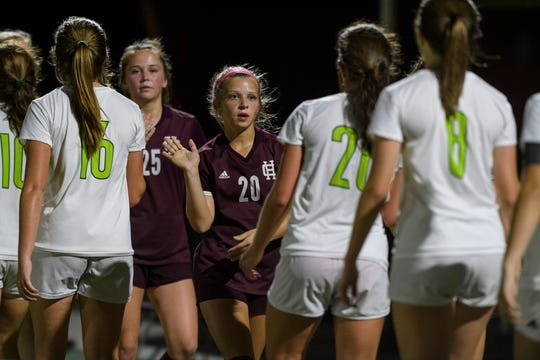 Henderson County's Morgan Green (20), center, and the rest of her team high-fives the Owensboro Catholic Lady Aces after the match at Colonel Field in Henderson, Ky., Thursday night, Oct. 3, 2019. The Colonels fell 2-1 to the Lady Aces.