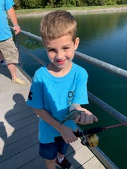 Henderson County resident Lucas Muensterman, 6, holds a fish at a camp in Scottsville, Ky. The camp is for children who have an autism diagnosis.