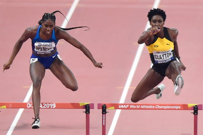 Ashley Spencer of the United States, left, and Rushell Clayton of Jamaica, compete during the women's 400 meter hurdles semifinal's at the World Athletics Championships in Doha, Qatar, Wednesday, Oct. 2, 2019. (AP Photo/Martin Meissner)