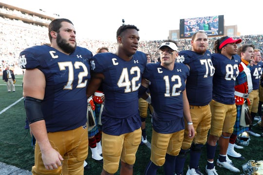 Notre Dame's Robert Hainsey (72), Julian Okwara (42), Ian Book (12) and Tommy Kraemer (78) sing after beating New Mexico 66-14  on Sept. 14, 2019 in South Bend, Indiana.