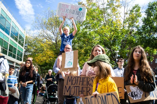 "Community members hold signs while listening to speeches during the climate strike for a ""Town-Gown Climate Accord"" hosted by the Iowa City Climate Strikers, Friday, Oct., 4, 2019, at the intersection of Dubuque Street and Iowa Avenue in downtown Iowa City, Iowa."