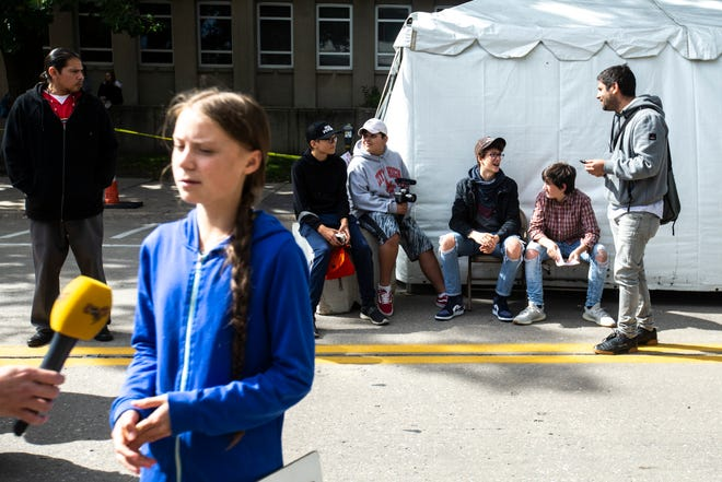 "Climate Strikers Massimo Biggers and Alex Howe do interviews while climate activist Greta Thunberg (foreground, left) does the same during the ""Town-Gown Climate Accord"" hosted by the Iowa City Climate Strikers, Friday, Oct., 4, 2019, at the intersection of Dubuque Street and Iowa Avenue in downtown Iowa City, Iowa."