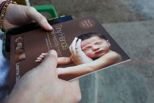 A sidewalk counselor holds onto one of the tracts they attempt to hand out to incoming patients at the Jackson Womens Health Organization clinic in Jackson, Miss., Wednesday, Oct. 2, 2019.  Jackson is trying to limit noise near the state's only abortion clinic. But opponents of a new ordinance say it unconstitutionally limits the free speech of people trying to talk women out of terminating their pregnancies. Nearby businesses say amplified sound from protesters and from the clinic itself is disruptive.(AP Photo/Rogelio V. Solis)