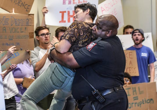 University of Mississippi police chief Ray Hawkins carries protester Cam Calisch out of a room where a news conference that was supposed to name former Mississippi Higher Education Commissioner Glenn Boyce as the new chancellor was to be held at the University of Mississippi, Friday, Oct. 4, 2019, in Oxford, Miss.
