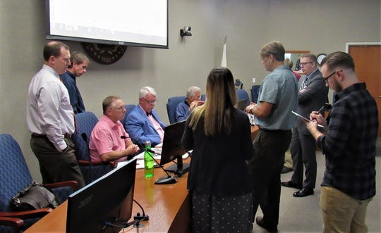 Town staff and aldermen looked over diagrams presented by architects for Admiral's Landing, the redevelopment project proposed for the old Phillips 66 gas station on Kingston Pike.