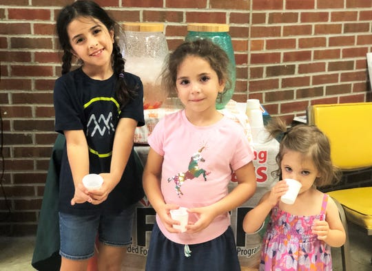 Olive, 7; Gillian, 5; and Miriam Grigsby, 2, try cups of fruit-infused water provided by Angie Beaty from Family & Consumer Sciences, UTExtension Institute of Agriculture. New Hopewell Elementary STEM Night, 10/3/2019