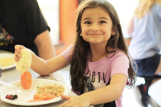 "New Hopewell Elementary student Stella Sims enjoys a meal provided by the Knox Area Medical Alliance, which has ""adopted"" the school this year. 10/3/2019"