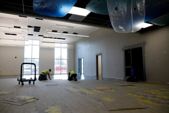 Workers install carpet squares in the media center of the new Thomas Ewing Junior High School Thursday, Oct. 3, 2019, in Lancaster.