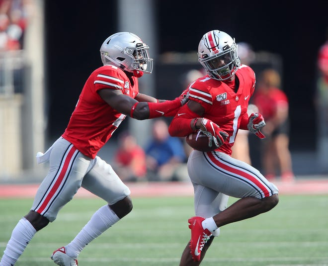 Ohio State cornerback Jeff Okudah is congratulated by safety Jordan Fuller following his interception against the Miami RedHawks. Okudah has made three interceptions in the last two games for the Buckeyes, who in one year have gone from one of the worst defenses in the country to one of the best.