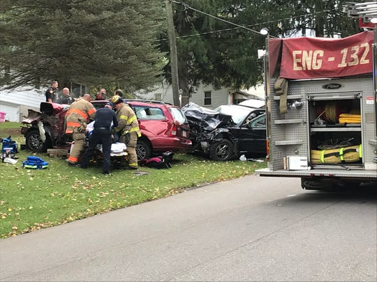 Mansfield firefighters assist a victim of a crash Friday on Davidson Street.  Deputies from the Richland County Sheriff's Office had received a description of a burglary in progress when the suspect crashed his vehicle.