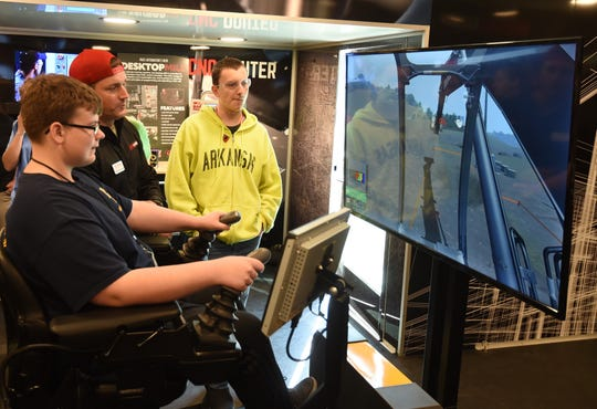 Sam Anderson, a ninth-grade Mountain Home student, operates an excavator simulator Thursday as Be Pro Be Proud tour director Scott Callaway and fellow ninth-grader Konrad Huston watch.