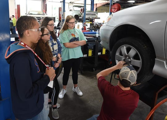 Mountain Home ninth-graders watch Thursday as the lug nuts on a car's wheel are put back on. The students then got to use a torque wrench to help tighten the lug nuts.