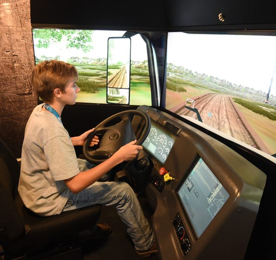 Mountain Home ninth-grader Kason Adkins drives a simulated semi truck Thursday in the Be Pro Be Proud mobile classroom on the campus of the ASUMH Technical Center.