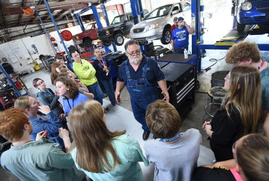 ASU-Mountain Home Technical Center instructor Curtis Taylor (center) talks to a group of Mountain Home ninth-graders Thursday about rotating a vehicle's tires.