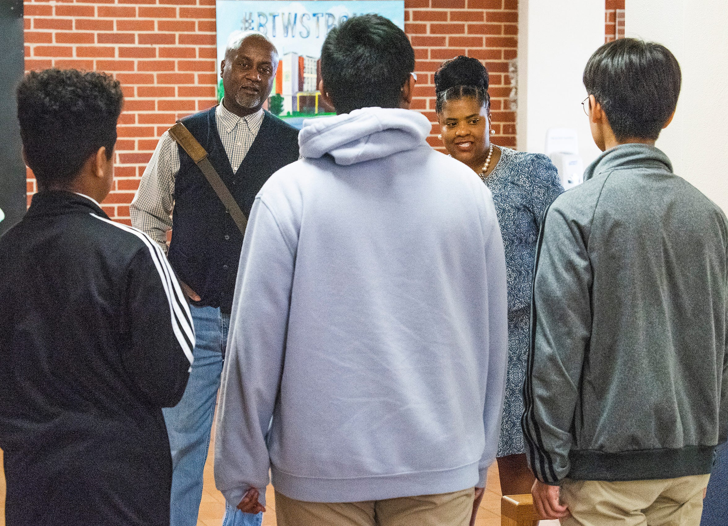 Local entrepreneur Boyd Stephens, left, and Booker T. Washington Magnet School Principal Quesha Starks, right, talk with computer students at the school in Montgomery, Ala., on Friday October 4, 2019.