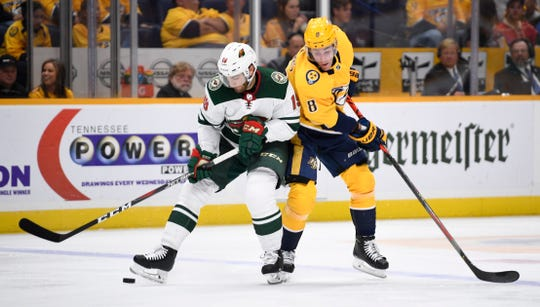 Minnesota Wild center Luke Kunin (19) and Nashville Predators center Kyle Turris (8) battle for the puck during the second period at Bridgestone Arena in Nashville, Tenn., Thursday, Oct. 3, 2019.