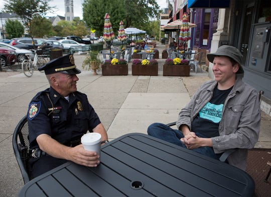 Bill Caskey, Granville's Chief of Police talks with local business owner, Jay Snyder, Friday afternoon in downtown Granville. Caskey says one of the biggest parts of his job is simply talking with people.