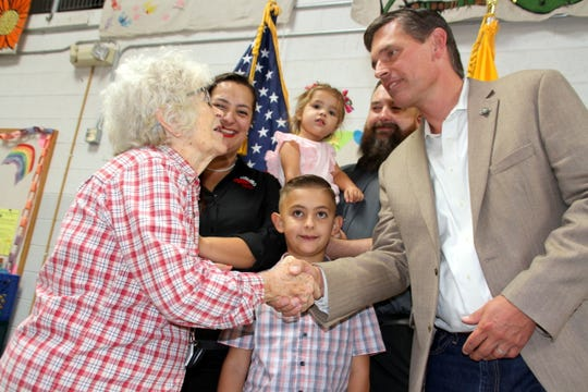 Grandmother Thelma Moore shakes the hand of U.S. Sen. Martin Heinrich during his visit to the Deming Migrant Relief Facility on Thursday.