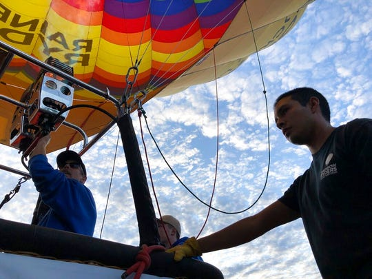 Elijah Sanchez, right, helps pilot Troy Bradley, left, prepare for liftoff in Albuquerque, N.M., on Tuesday, Oct. 1, 2019. Sanchez, 20, will be among the youngest pilots to launch as part of this year's Albuquerque International Balloon Fiesta. The nine-day event is expected to draw several hundred thousand spectators and hundreds of balloonists from around the world. It will kick off Oct. 5 with a mass ascension.