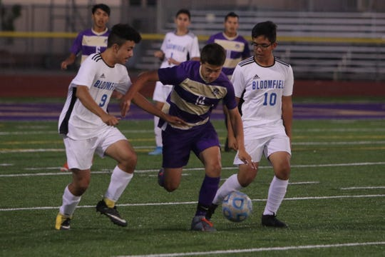 Kirtland Central's Dimas Villalobos-Hunt tries to fend off Bloomfield's Jesus Jaquez (9) and Luis Gonzalez (10) in pursuit of the ball during Thursday's boys soccer match at Bill Cawood Field in Kirtland.