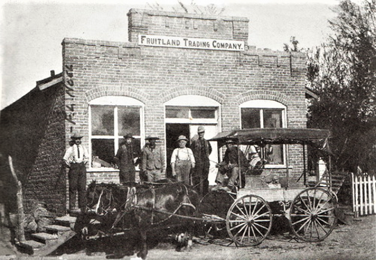 Frank Noel, left, and Eli Rufus Cline, fourth from left, stand alongside several other men outside the Fruitland Trading Company in this photo, circa 1908.