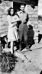 Newlyweds Polly and Jack Cline stand outside the Bisti Trading Post holding a dog in this photo, circa 1931.