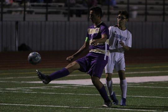 Kirtland Central's Jaxon Manning passes the ball back the other way against Bloomfield's Daniel Rubio during Thursday's boys soccer match at Bill Cawood Field in Kirtland.
