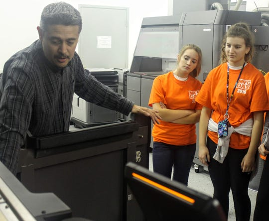Joe Gonzales, a technical specialist at Linear AMS, shows Holmes Middle School students how one of the printers works at their Livonia facility for Manufacturing Day Friday.