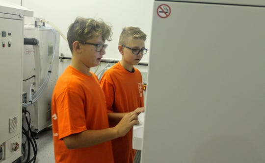 Seventh graders Connor Buchanan and Caden Yacura look at one of the machines at Linear AMS in Livonia on Friday for Manufacturing Day.