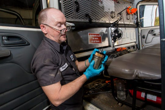 Wayne Bryan, a fleet maintenance technician, replaces a fuel filter Friday while doing preventive maintenance on a truck at the Escambia County Road Department in Cantonment.