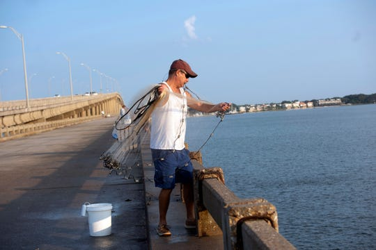 James Garner looks to snare a few baitfish while fishing from the old Bob Sikes fishing pier on Friday. The pier has previously received funding from restitution paid by BP for the Deepwater Horizon oil spill.