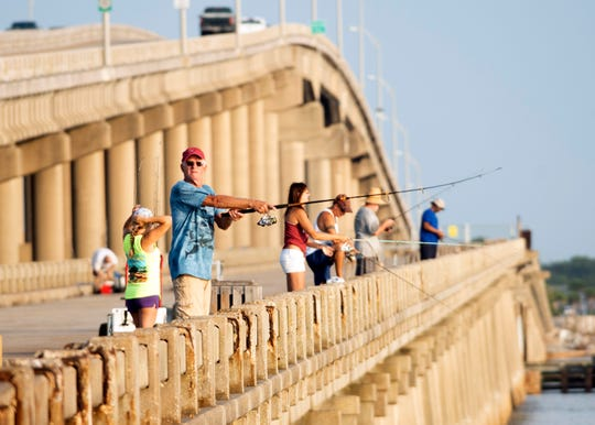 Jim Williams joins other anglers looking for the catch of the day while fishing from the old Bob Sikes fishing pier on Friday. The pier has previously received funding from restitution paid by BP for the Deepwater Horizon oil spill.
