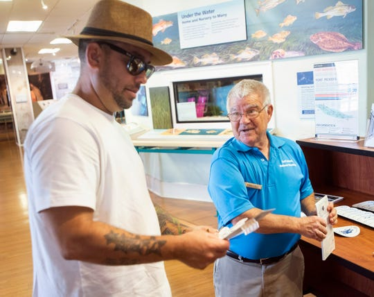 National Park Service volunteer Roman Stanley informs visitor Jerson Lugo about the Perdido Key beach mouse and offers him a magnet on Friday.