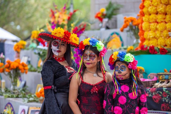 Women with painted faces participate in the Mesa Arts Center's Dia de Los Muertos celebration near Phoenix.