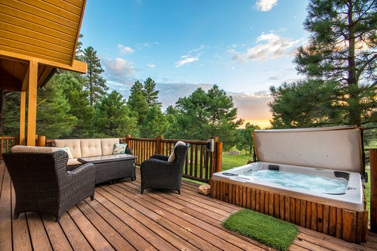The expansive deck features a hot tub.