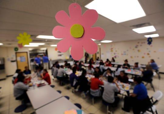 Decenas de niños migrantes almuerzan en la instalación migratoria de San Benito, Texas.