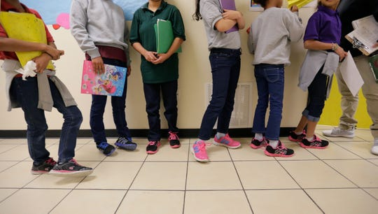 Niños migrantes hacen fila en la instalación migratoria de San Benito, Texas.