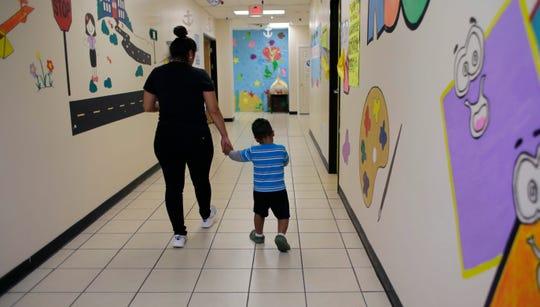Un niño es supervisado por una trabajadora social en la instalación migratoria de San Benito, Texas.