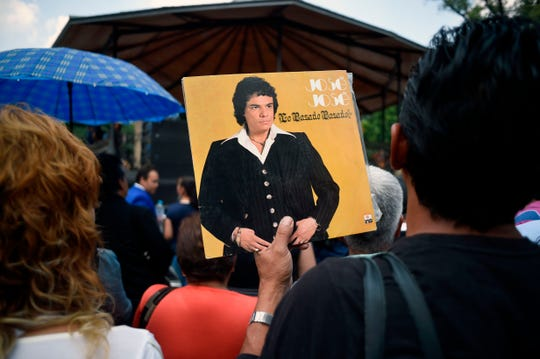 Fans de José José sostienen uno de sus discos en el funeral de Miami.