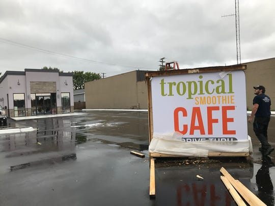 Northern Sign Co. employee Josh Hansen walks around the new Port Huron Tropical Smoothie Cafe sign on 24th Street on Oct. 4, 2019.
