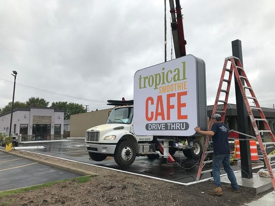 Northern Sign Co. employee Nathan Zubal gets ready to put up the Port Huron Tropical Smoothie Cafe sign on 24th Street on Oct. 4, 2019.