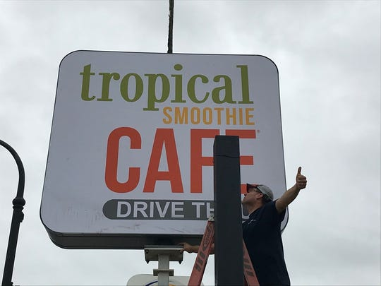 Northern Sign Co. employee Nathan Zubal gives fellow employee Josh Hansen a signal while they put up the Port Huron Tropical Smoothie Cafe sign on 24th Street on Oct. 4, 2019.