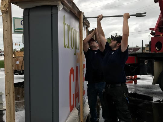 Northern Sign Co. employees Nathan Zubal and Josh Hansen get ready to put up the Port Huron Tropical Smoothie Cafe sign on 24th Street on Oct. 4, 2019.
