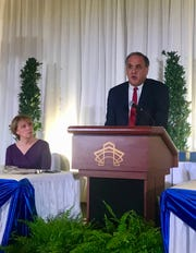 Michael Kilian, executive editor of the Democrat & Chronicle, speaks about the D&C's mobile newsroom initiative at Ibero's annual luncheon on Friday. Listening at left is WROC (Channel 8) anchor Maureen McGuire.