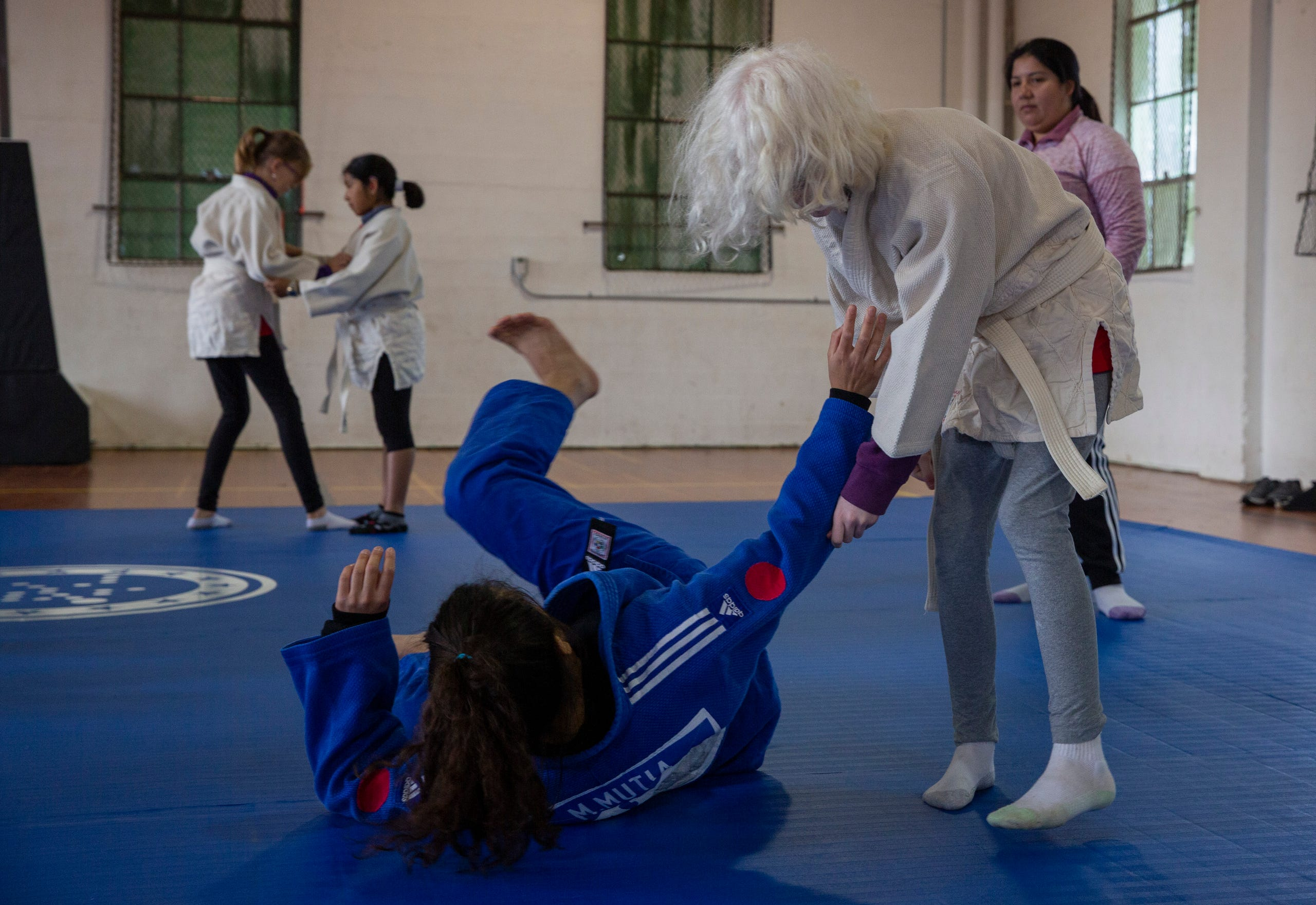 "Fifth-grader Emily Underwood practices a move on Judo World Champion, Liana Mutia, at the Oregon School for the Deaf in Salem, Oct. 4, 2019. NWABA, the Northwest Association for Blind Athletes, hosted a ""Paralympic experience"" for students with visual impairments in the state. After the Oregon School for the Blind closed in 2009, many visually impaired students and their families lost access to state-funded resources, like sports programs. The BVIS (Blind Visually Impaired Student) Fund gives programs like NWABA funds to enhance the lives of low vision/blind children across the state."