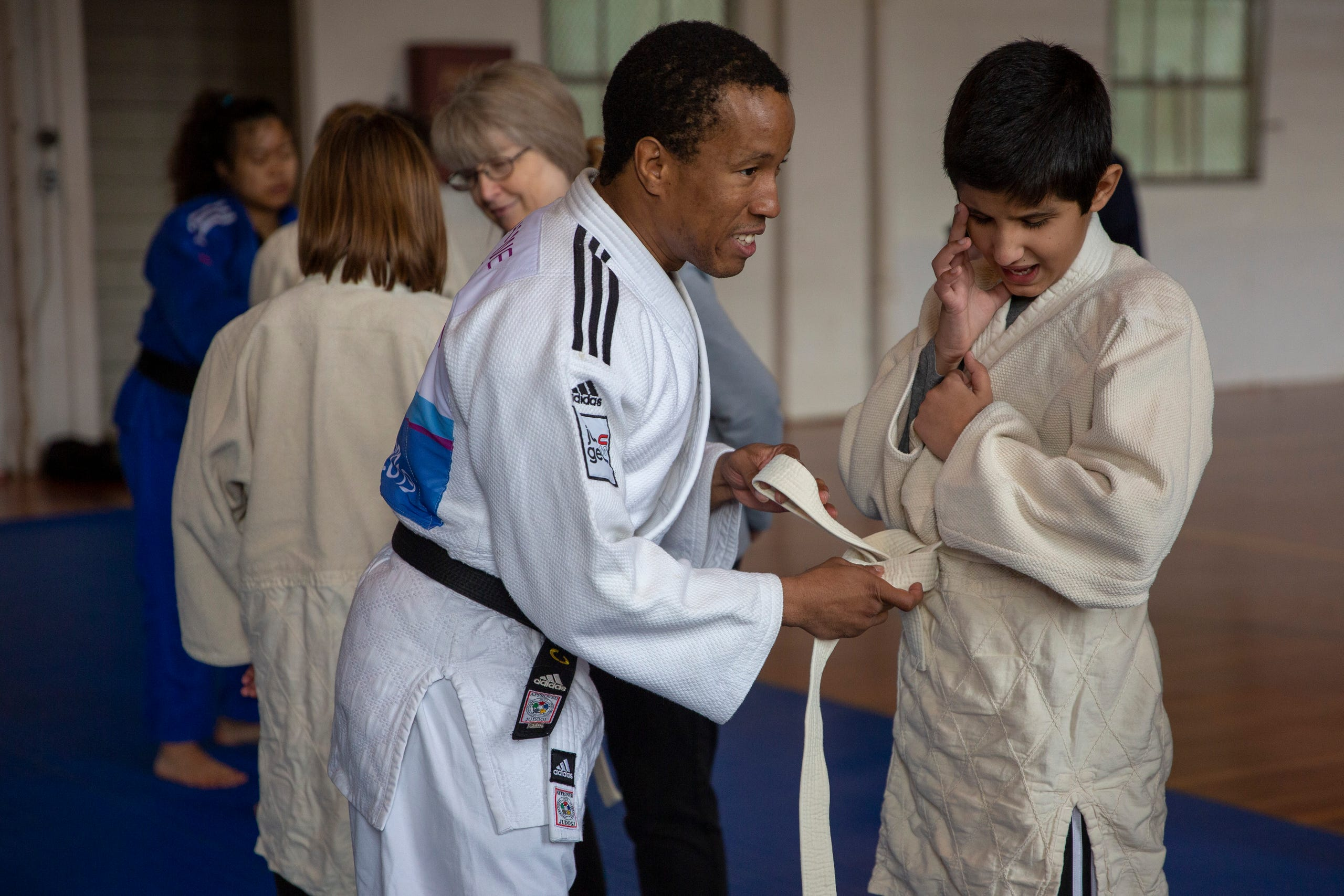 "Instructor and Judo Paralympian Ron Hawthorne ties the robe of sixth-grader Saifullah Tahirkheli at the Oregon School for the Deaf in Salem, Oct. 4, 2019. NWABA, the Northwest Association for Blind Athletes, hosted a ""Paralympic experience"" for students with visual impairments in the state. After the Oregon School for the Blind closed in 2009, many visually impaired students and their families lost access to state-funded resources, like sports programs. The BVIS (Blind Visually Impaired Student) Fund gives programs like NWABA funds to enhance the lives of low vision/blind children across the state."
