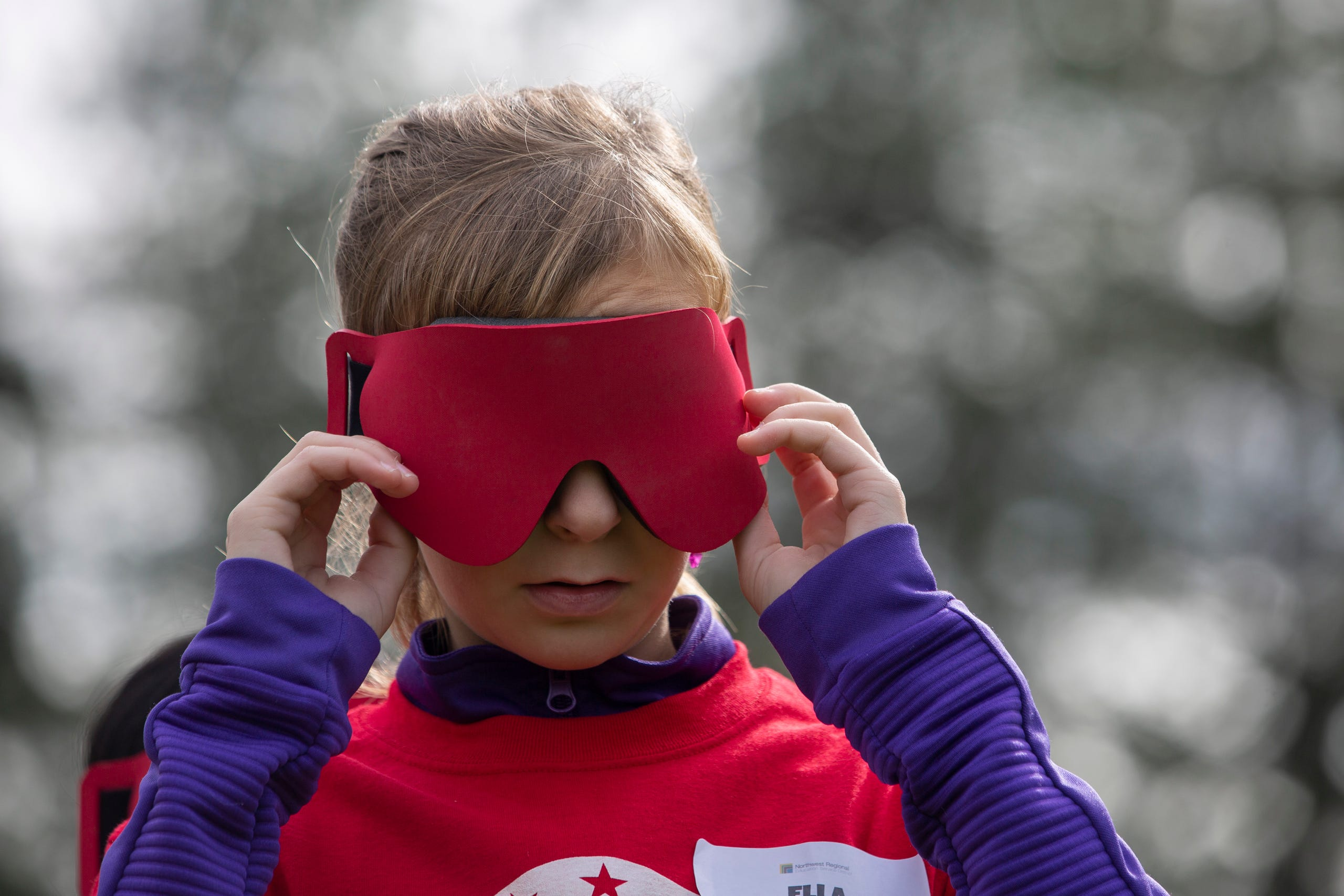 "Ella Shrout, a 7th grader, puts on the blindfold required to play beep kickball at the Oregon School for the Deaf in Salem, Oct. 4, 2019. NWABA, the Northwest Association for Blind Athletes, hosted a ""Paralympic experience"" for students with visual impairments in the state. After the Oregon School for the Blind closed in 2009, many visually impaired students and their families lost access to state-funded resources, like sports programs. The BVIS (Blind Visually Impaired Student) Fund gives programs like NWABA funds to enhance the lives of low vision/blind children across the state."