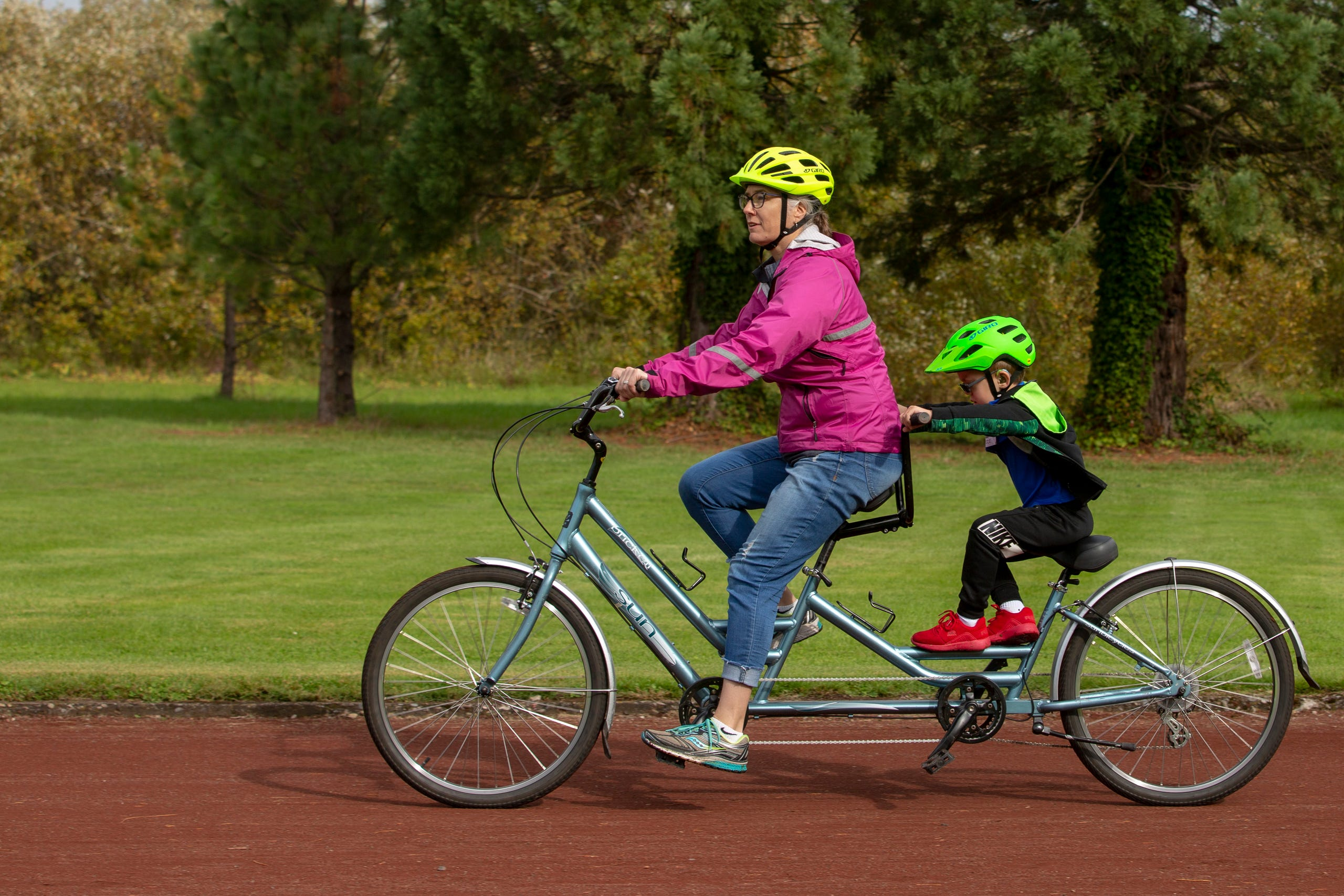 "Tandem biking instructor Kate Dillsworth and first-grader Hugo Olsen take a lap around the track at the Oregon School for the Deaf in Salem, Oct. 4, 2019. NWABA, the Northwest Association for Blind Athletes, hosted a ""Paralympic experience"" for students with visual impairments in the state. After the Oregon School for the Blind closed in 2009, many visually impaired students and their families lost access to state-funded resources, like sports programs. The BVIS (Blind Visually Impaired Student) Fund gives programs like NWABA funds to enhance the lives of low vision/blind children across the state."