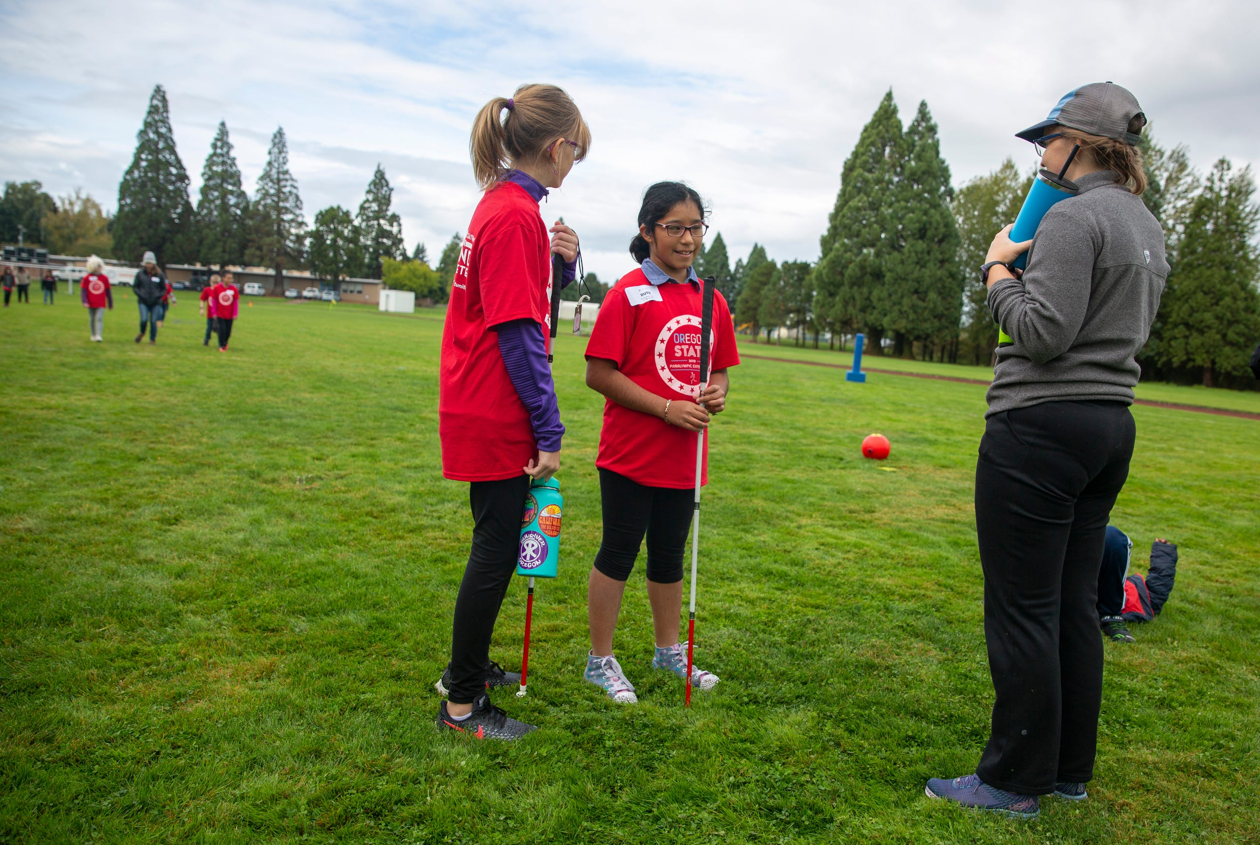 "Ellen Shrout, in 7th grade, and Ruth Gongora, in 6th, talk to a beep kickball instructor at the Oregon School for the Deaf in Salem, Oct. 4, 2019. NWABA, the Northwest Association for Blind Athletes, hosted a ""Paralympic experience"" for students with visual impairments in the state. After the Oregon School for the Blind closed in 2009, many visually impaired students and their families lost access to state-funded resources, like sports programs. The BVIS (Blind Visually Impaired Student) Fund gives programs like NWABA funds to enhance the lives of low vision/blind children across the state."