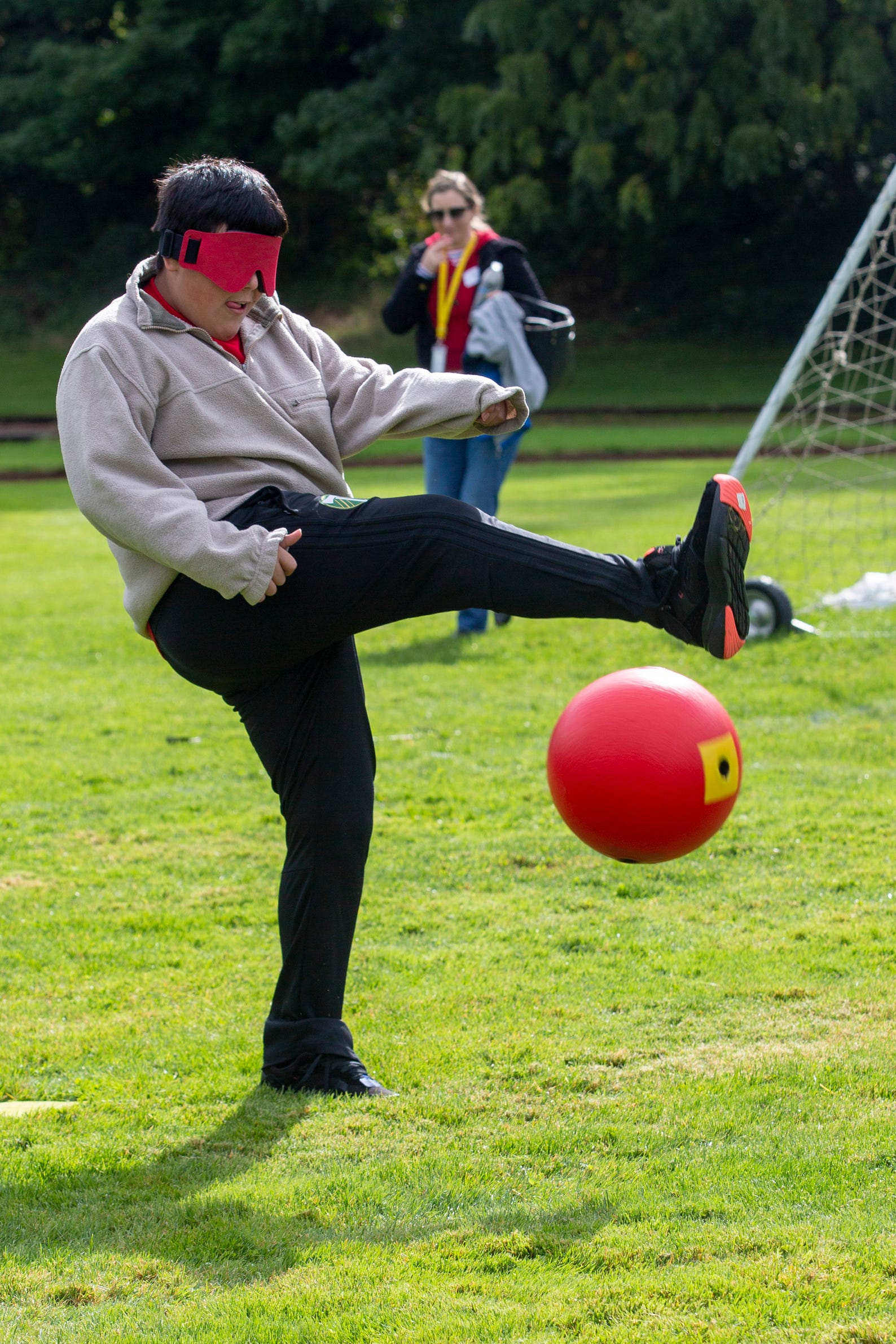 "Luis Alvarez-Castaneda, a 6th grader, takes a mighty kick during beep kickball at the Oregon School for the Deaf in Salem, Oct. 4, 2019. NWABA, the Northwest Association for Blind Athletes, hosted a ""Paralympic experience"" for students with visual impairments in the state. After the Oregon School for the Blind closed in 2009, many visually impaired students and their families lost access to state-funded resources, like sports programs. The BVIS (Blind Visually Impaired Student) Fund gives programs like NWABA funds to enhance the lives of low vision/blind children across the state."